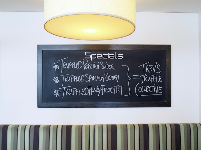 Blackboard menu that reads: Specials - Truffled Pocini Slider, Truffled Spinach Benny, Truffled Honey French Toast = Trevs Truffle Collective