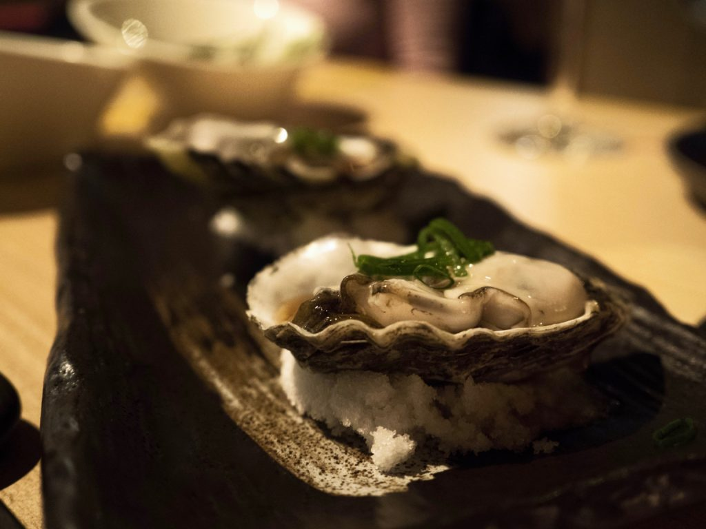 A raw oyster sitting on a bed of salt