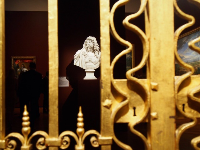 Golden gild gates with marble statue in background