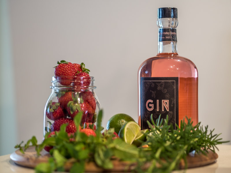 A bottle of pink gin is sitting on a wooden board that also has lime segments, mint, rosemary and a jar of strawberries, l
