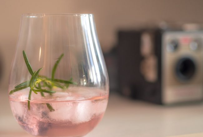 A glass is quarter filled with pin gin, ice-cubes and a sprig of rosemary. In the background is a vintage camera.