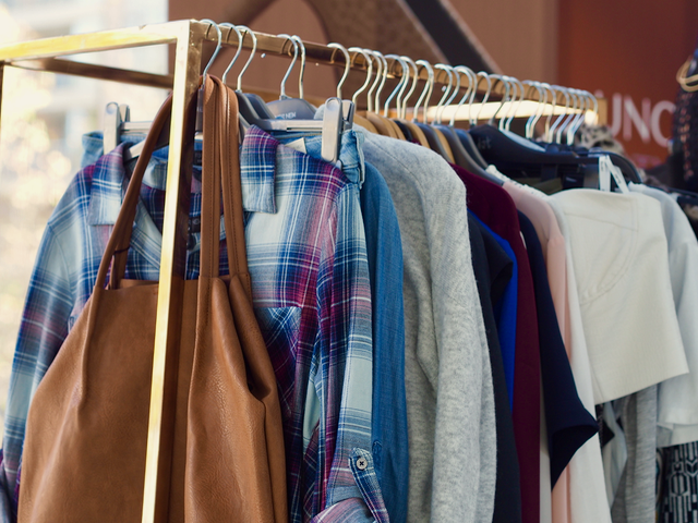 A clothes rack with an assortment of clothes and a brown bag.