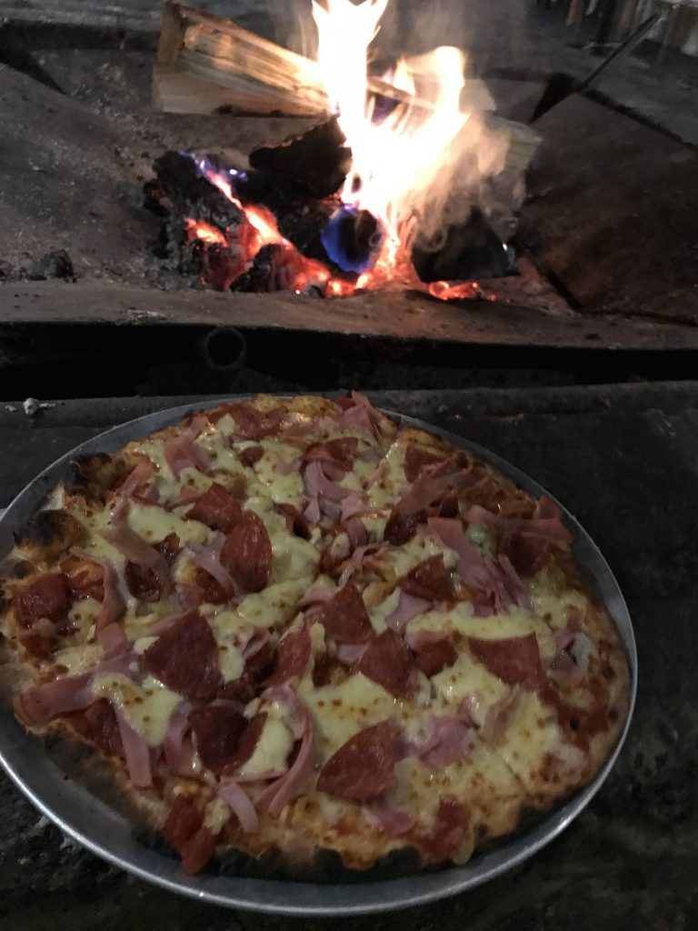 Meat lovers pizza by the fire at Corin Forest