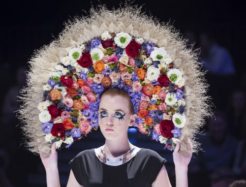 Female model wears a large floral headpiece.