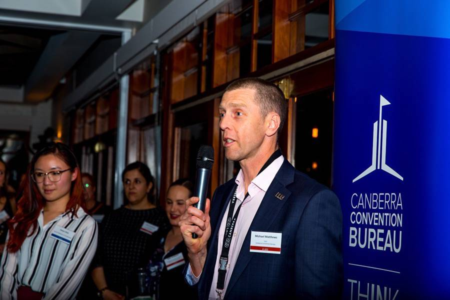 Man wearing suit holds a microphone and talks to a group of people. The sign behind him reads Canberra Convention Bureau.