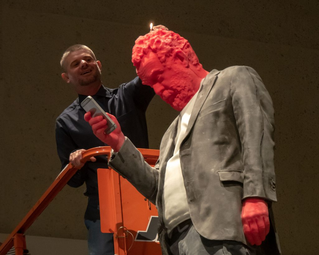 Nick Mitzevich, gallery director, gives life to 'Francesco' as he lights the sculpture