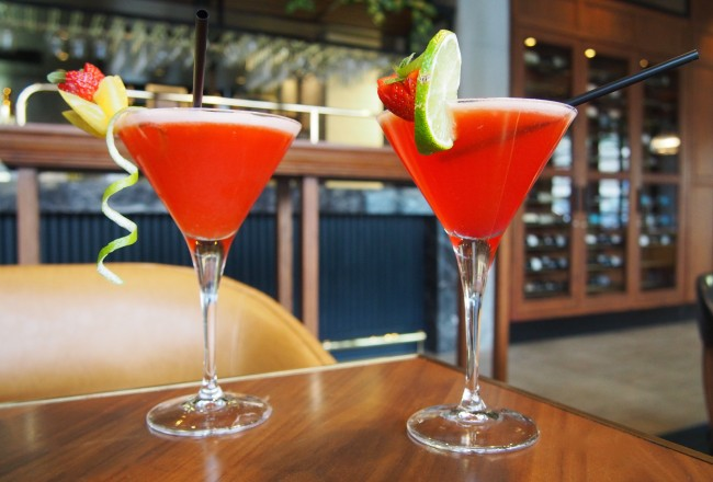 Two red cocktails with fruit.