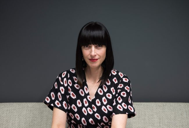 Female sitting on a couch, she is wearing a patterned top.