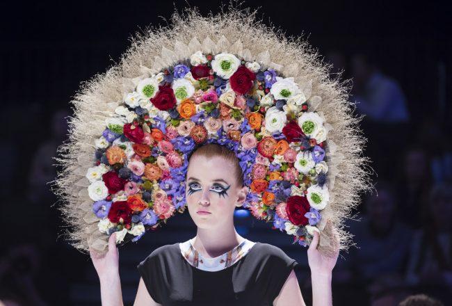 Female model wears a large floral headpiece.